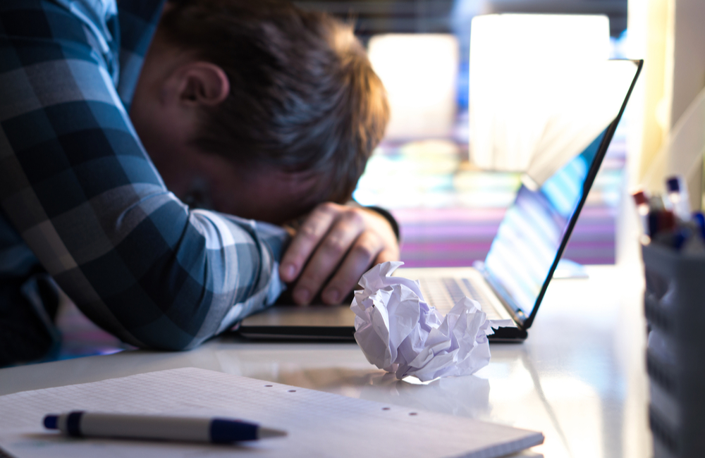 A frustrated writer with his head on the desk. An open laptop and a crumpled sheet of paper around him