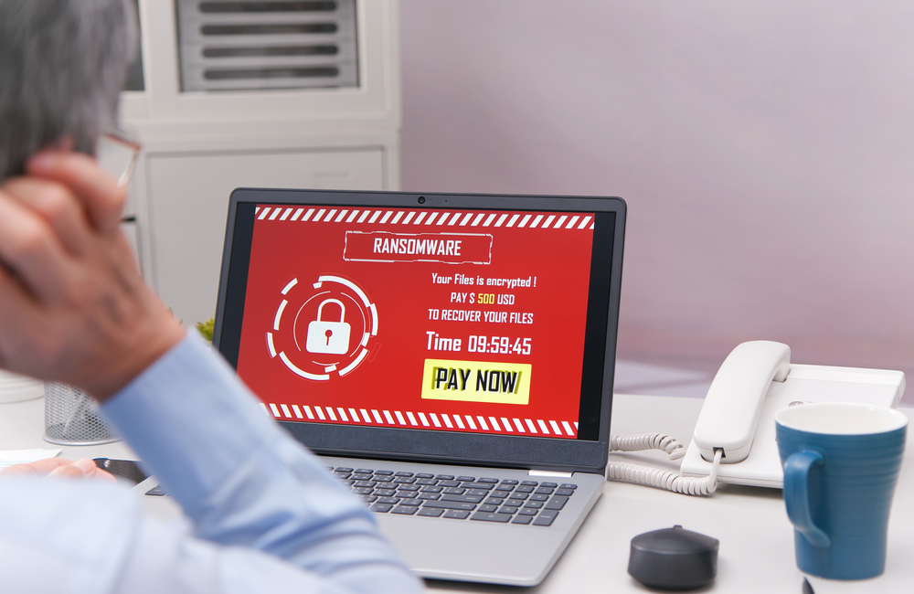 A small business owner sits in front of a laptop displaying s ransomeware message