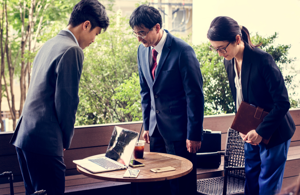 Three Japanese businesspeople bow as a sign of respect