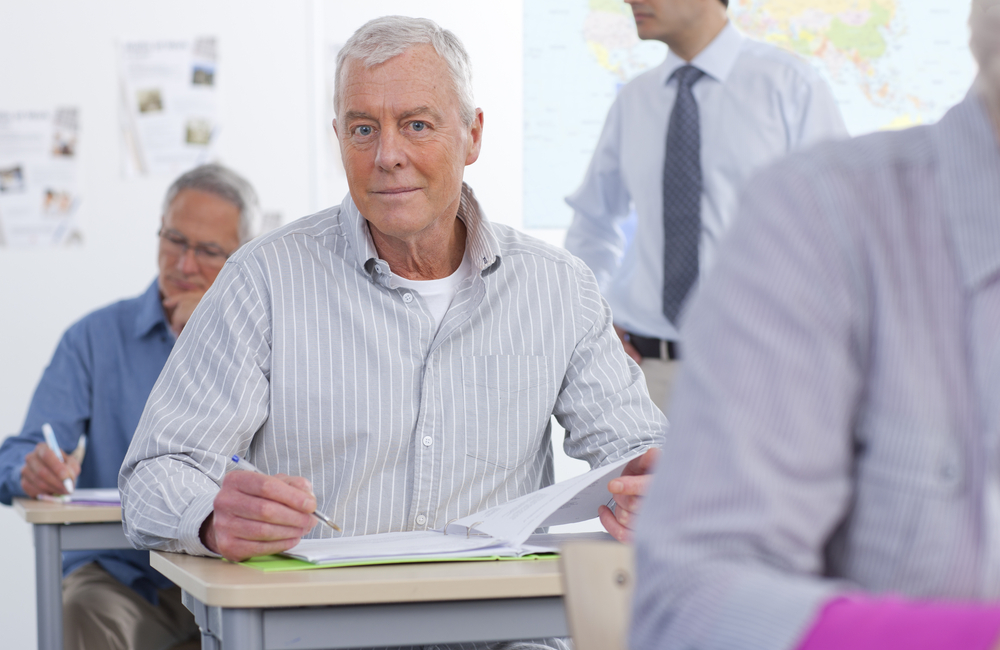 An older man sits at a classroom desk engaged in his studies
