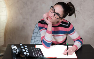 A screenwriter sits at a desk with a pen and pad of paper pondering good character names for her screenplay. A film slateboard sits on the desk beside her.