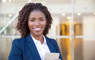 Smiling businesswoman stands in an office lobby holding a tablet.