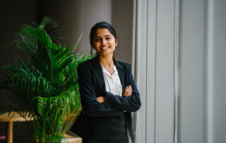 Smartly dressed, smiling businesswoman stands in her office.