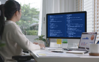 A computer scientist sitting at her desk studies code on her computer monitor as she works on a new software program.